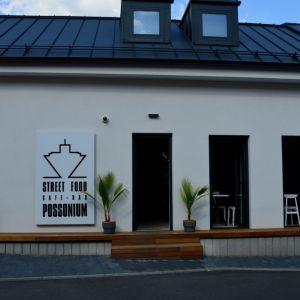 Budova dobre komunikuje s dopravne ukľudnenou ulicou, rošt pozdĺž fasády poskytuje ďalšie možnosti sedenia.