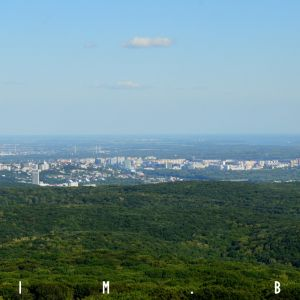Zľava Mlynská dolina, centrum mesta a Petržalka, v diaľke Podunajská nížina preťatá Dunajom a zdržou Hrušov